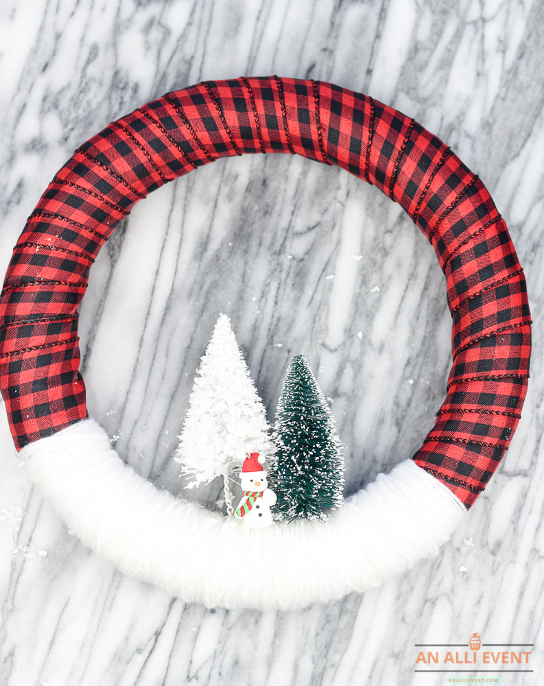 12+ of my favorite Christmas wreath tutorials, including this Snowy Scene Wreath with Checked Ribbon Wreath! Learn how to make wreaths to decorate your home, everywhere from your front door to your kitchen! The wreaths use everything from fresh evergreens to these puzzle pieces (a genius way to save money when you make your wreath. You gotta see it!) and everything in between. Check it out to get some fabulous ideas.