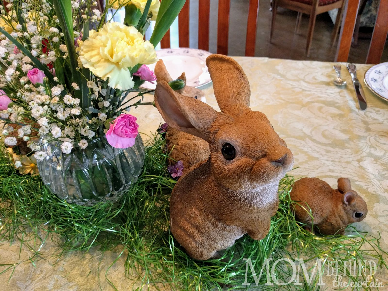 Easter rabbit collection arranged with real flowers and Easter basket grass.