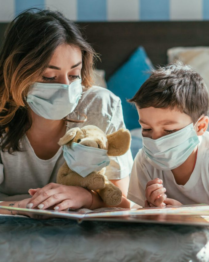 Mother and kid read books during the Covid pandemic to help understand pandemics and historical childhood illnesses.