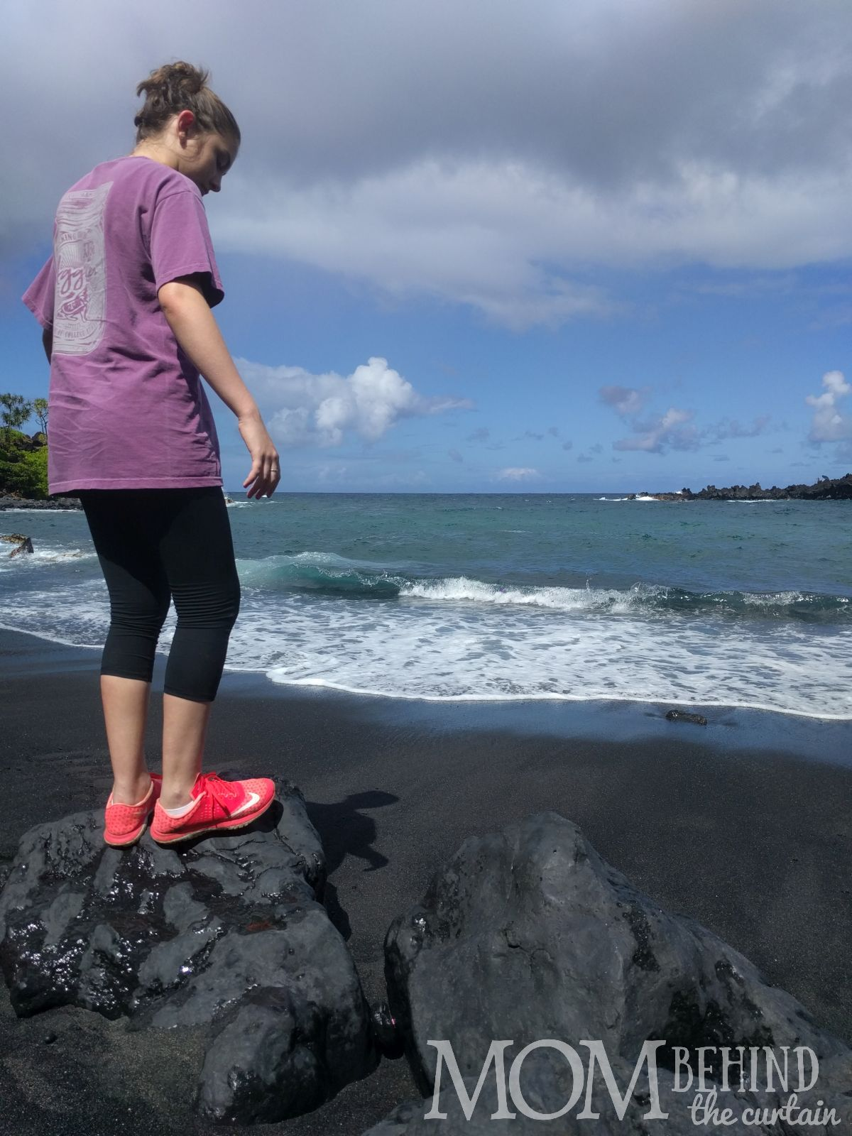 standing on rocks on black sand beach, Maui, Hawaii